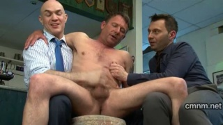 Suited men tug naked guy's cock