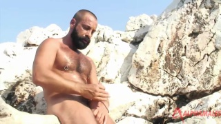 Hairy guy jerking off on rock