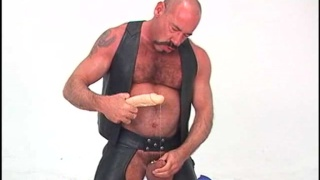 Hairy stud oils up his brown hole and shoves a dildo in his ass