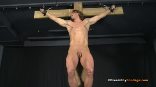 Blond muscle stud crucified to cross