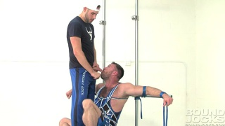 muscle hunk Aaron Cage is tied to the poles
