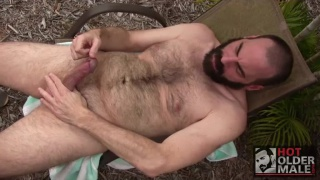 bear man Steve Sommers strokes his dick outdoors