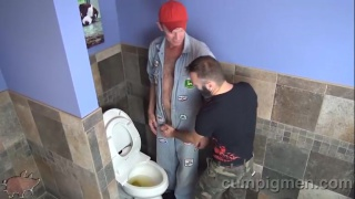 two guys swapping head in a public toilet