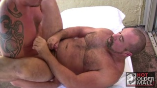 hairy men bumping bellies on massage table