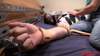 clothed man blindfolded and strapped to bed