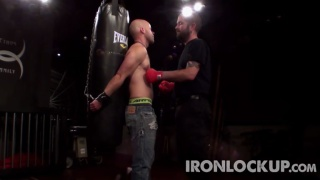 slave tied to punching bag and gut punched