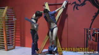slave boy in denim restrained on a wooden cross