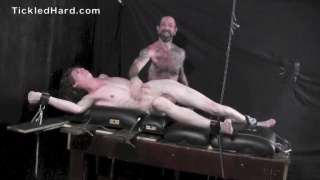 ROGER MICHAELS strapped to the tickling table
