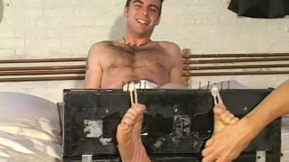 bondage master restrains guy's feet up and tickles him silly