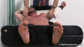 bearded salesman strapped into the tickling chair