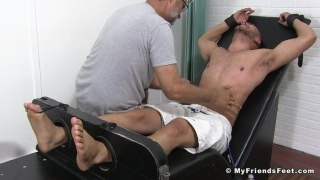 guy in tickling chair requires a bit of manhandling