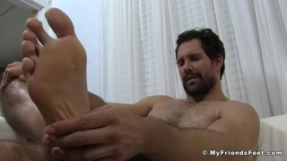 handsome bearded guy rubs his sore bare feet