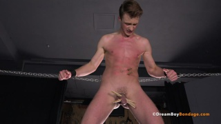 slave boy chained in dungeon with clothes pegs on his balls