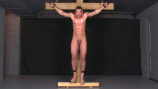 naked hunk lance bound to a wooden cross