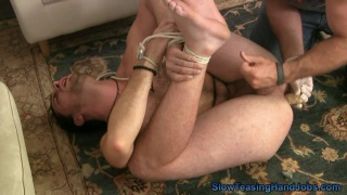 jacking off a bound dude with a dildo in his butt