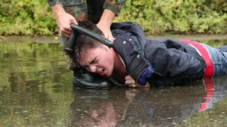soldier tormenting young recruit in a creek