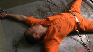chained prisoner in orange coveralls spread eagle on floor