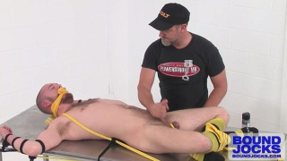 Bound jock Jordan Foster tied to table in a yellow jock strap