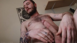 furry inked dude strokes his long dick