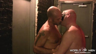 bald men fuck in corner of a leather bar
