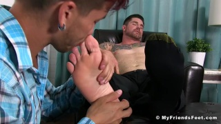 Justin Case on his knees sniffing and licking bare feet