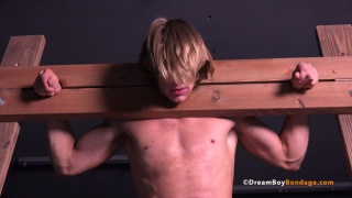 blond straight guy in wooden stockade gets flogged