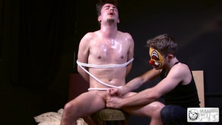 smooth lad tied to chair and stroked by guy in clown mask