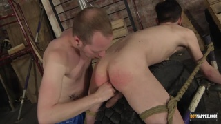 slave boy tied up and bent over a tire