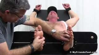 Dev tied up in the tickling chair