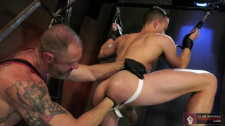 Muscled leatherman dominates young stud