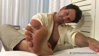 handsome man rubs his feet after work