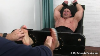 beefy bald guy strapped into the tickling chair