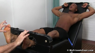 Trent King strapped into the tickling chair