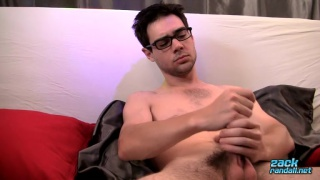 Zack Randall strokes his large uncut cock with both hands