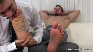 bare-chested hunk sits back and gets his big feet licked