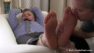 Brenden Cage tied to sofa for foot worshipping session