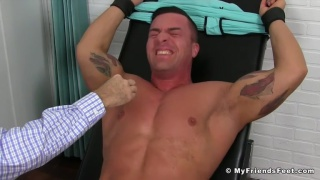 braden Charron strapped into the tickling chair
